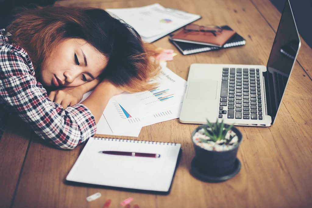 Woman-Tired-Sleeping-At-Desk